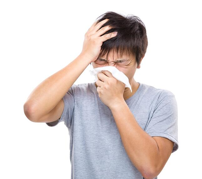 Sneezing and headache of asian man with chronic sinusitis.
